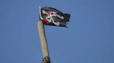 Jolly Roger danger Pirate flag develops against the blue sky