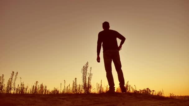 Man travel silhouette. Man shows his hand in the distance standing on mountain silhouette sunlight sunrise
