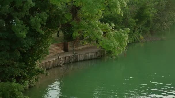 wooden pier next to a river of water and green forest trees. Nature beautiful landscape