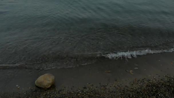 moře oblázková pláž s barevných kamenů, průzračnou vodu s pěnou, na teplý večer