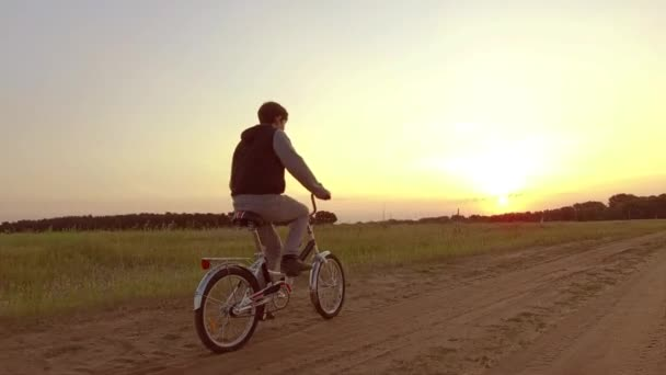Boy teenager riding a bicycle. Boy teenager riding a bicycle goes to nature along the path video steadicam shot motion