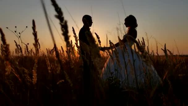 Romantikus esküvő a fiatal pár sziluettje. szerető pár a sunset férfi és a lány sziluettje