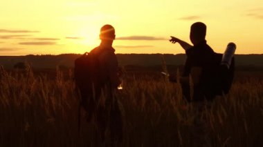two tourists silhouettes. two tourists at sunset are standing in the field watching cards in the smartphone. tourists drink water silhouette nature from a plastic bottle slow motion video
