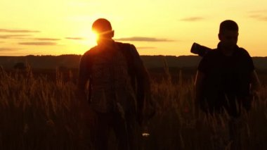 two tourists silhouettes. two tourists go at sunset. tourist nature silhouette slow motion video