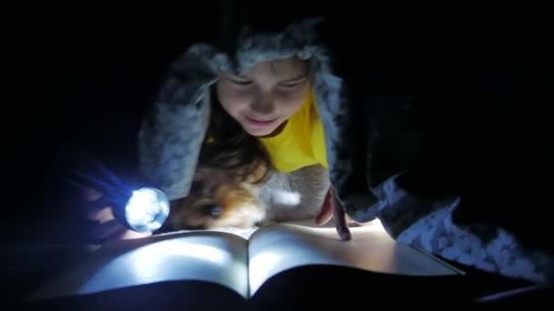 dospívající dítě a pes čtení dívka čte knihy v noci dítě s baterkou pod dekou