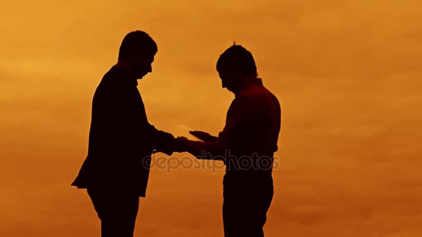 businessman discussion sunset silhouette sunlight standing clipboard concept. two businessman men are in talks looking at slow video