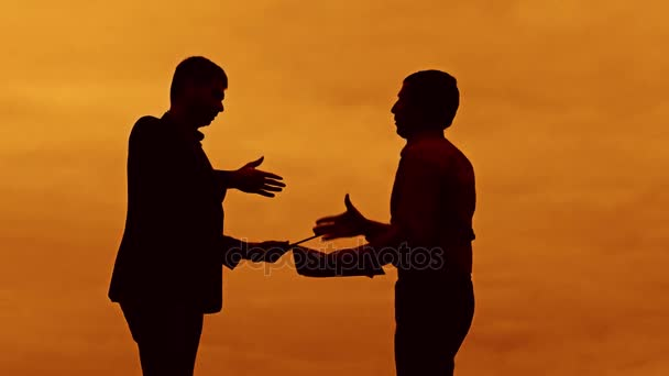 businessman discussion sunset silhouette sunlight standing clipboard concept. two businessman men shake hands meeting are in talks looking at outdoors slow motion video