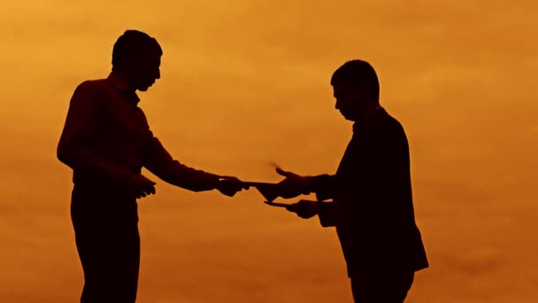 businessman discussion sunset silhouette sunlight standing clipboard concept. two businessman men swearing conflict outdoors fight looking at slow motion video