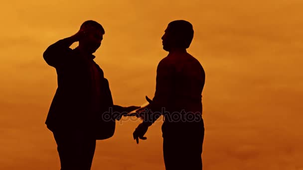 businessman discussion sunset silhouette sunlight standing clipboard concept. two businessman men shake hands meeting are in talks outdoors looking at slow motion video