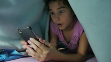 girl teenager and dog night under a blanket playing in a smartphone. little girl before bed lies in bed surfing on indoor the internet