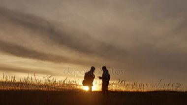people go group travel of tourists field nature of a sunset silhouette two travel people . tourists nature people group lifestyle go