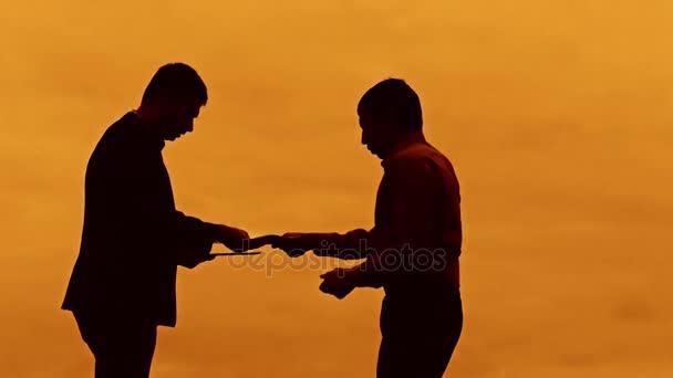 Geschäftsmann Diskussion Sonnenuntergang Silhouette Sonnenlicht stehen Zwischenablage bösen Boss Konzept. zwei Unternehmer Männer fluchen im freien Konflikt Kampf Slow-Motion-video anschauen