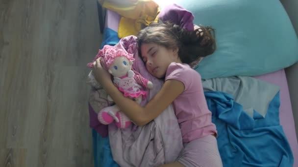 Rozkošný dívka noc spát v interiéru rozkládací pohovku a obejmout panence. brunetka dospívající dívka roztomilý spí na posteli
