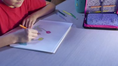 Little girl indoors painting at table. schoolgirls girl teenager the draws drawing with pencils