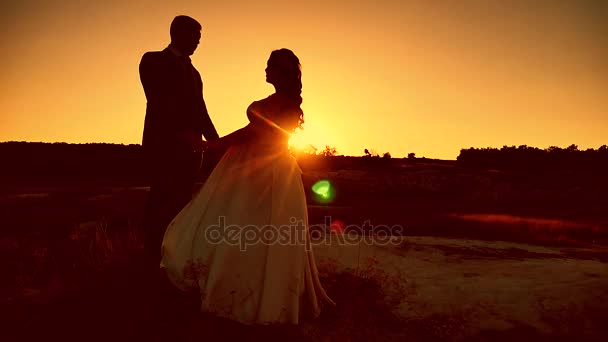 Silhouettes newlyweds of lovers men and women stand face to face on the background of sunset sky