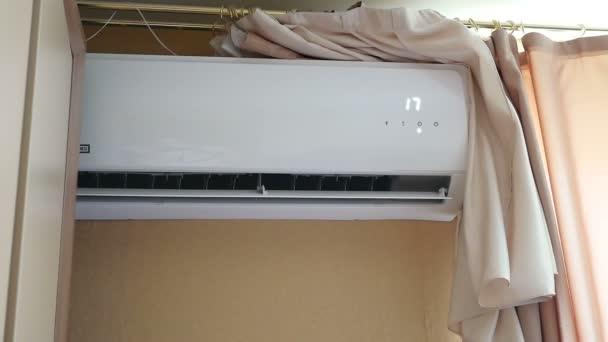 Klimaanlage im Zimmer mit Frau, die Fernbedienung bedient. Klimaanlage mit Fernbedienung