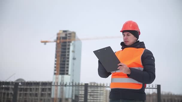 builder architect man worker in helmet and orange vest against the background of a multi-storey house crane winter worker