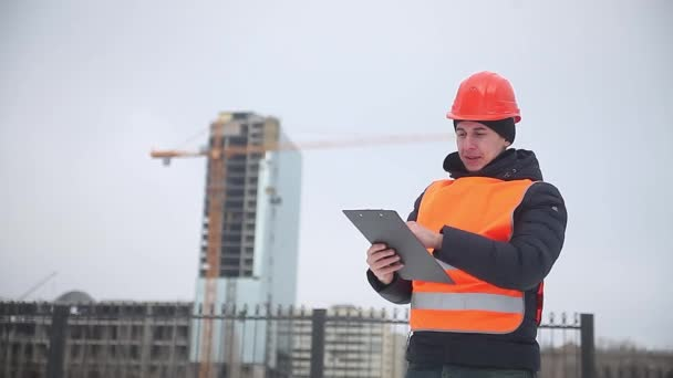 builder architect man worker in helmet and orange vest against the background of a multi-storey winter house crane worker