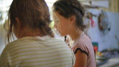 girls are preparing children in the kitchen. two girl friends preparing food in the kitchen indoors