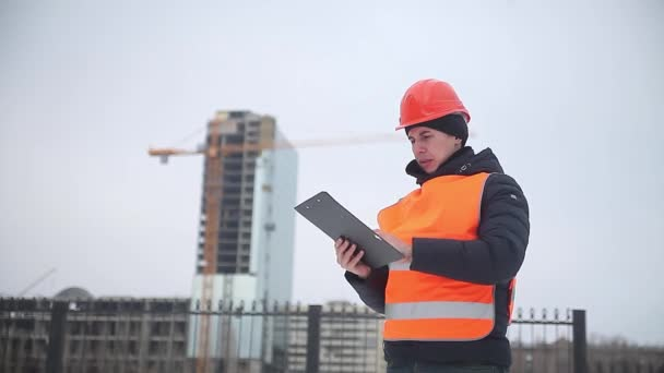 builder architect man worker in helmet and orange vest against the background of a multi-storey house crane worker winter