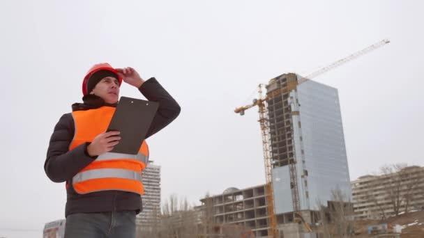 Tvůrce zla architekt muž pracovník třese rukou helmu a oranžovou vestu na pozadí zimní vícepodlažní dům pracovník jeřábu