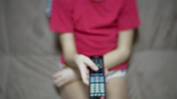Ruční dívka dítě drží tv dálkové ovládání a procházení programy v televizi. Dospívající dívka sledování Tv v obývacím pokoji nebo ložnici. teen dívka uvnitř tv dálkové ovládání