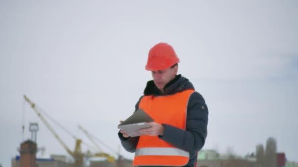 stavitel architekt muž v přilbě s tabletem na staveništi. stavební průmysl dělník v zimě budování domu životní styl