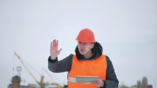 Tvůrce předák mává rukama člověka architekt v přilbě s tabletem na staveništi. stavební průmysl dělník v zimě budování životní styl domu venku