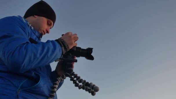 Siluetta del fotografo al tramonto. Cineoperatore dei video di fotografo uomo spara video sullo stile di vita tramonto natura