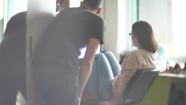 Koncentrovaná pár mladých kolegů pracujících v moderní kanceláři. Dva spolupracovníky diskutovat o jejich práci, práci s dokumenty. muž a žena pracující v kanceláři na počítači volná forma oblečení
