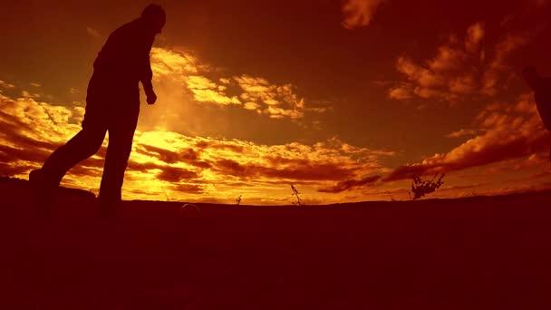 dva muži fotbal hráč hraje s míčem během západu slunce silueta zpomalené video. muži hraje Evropský fotbal na přírodě západ slunce silueta životní styl Outdoor