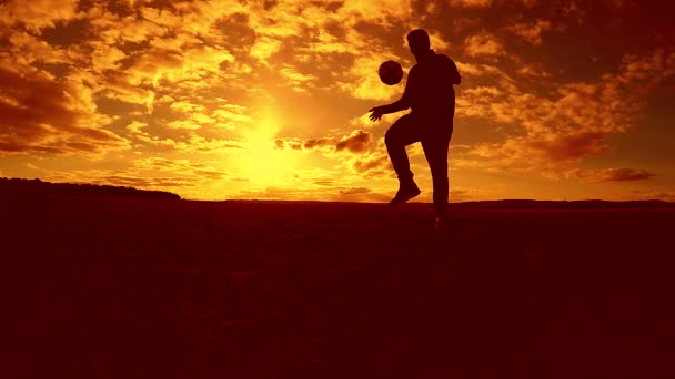 fotbalista nádivka míč silueta životní styl člověka kopne míč ve vzduchu s slunce pozadí. člověk hrát fotbal na západu slunce přírodní sluneční světlo silueta venku zpomalené video