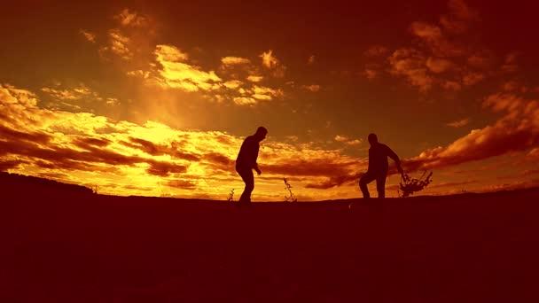 dva muži fotbalista hrát s míčem venku během západu slunce silueta zpomalené video. muži hraje Evropský fotbal na životní styl příroda západu slunce silueta