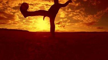 fotbalista nádivka míč siluetu člověka kopne životní styl míče ve vzduchu s slunce pozadí. člověk hrát fotbal na západu slunce přírodní sluneční světlo silueta venku zpomalené video