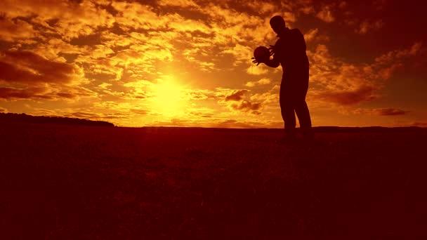 fotbalista nádivka míč siluetu člověka kopne míč ve vzduchu s slunce pozadí. muž si hraje fotbal na životní styl slunce přírodní sluneční světlo silueta venku zpomalené video
