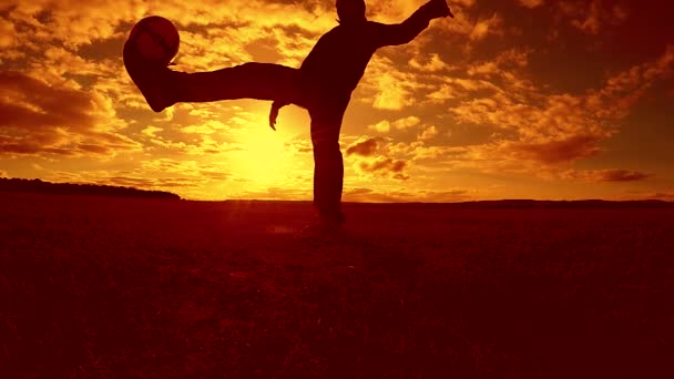 soccer player stuffing ball silhouette man kicks lifestyle ball in the air with sunset background. man playing soccer at sunset nature sunlight silhouette outdoors slow motion video