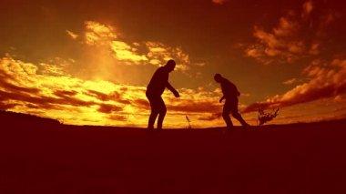 dva muži fotbal hráč hraje s míčem během západu slunce silueta zpomalené video. muži hrají evropské venku fotbal na příroda západu slunce silueta životní styl