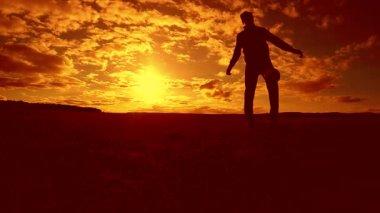 fotbalista nádivka míč siluetu člověka kopne míč ve vzduchu s slunce pozadí. člověk hraje fotbal životní styl při západu slunce přírodní sluneční světlo silueta venku zpomalené video