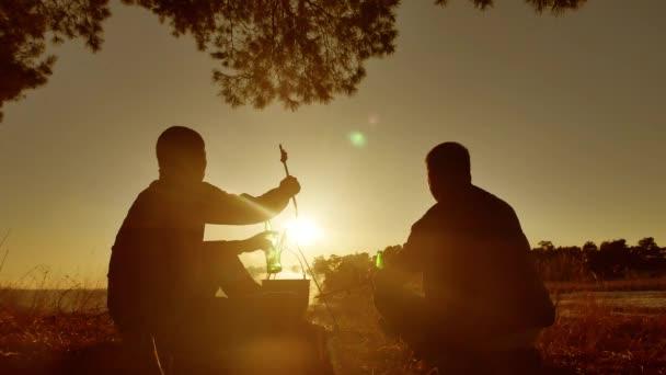 két turisták sör ül életmód, a tábortűz fél természet kemping silhouette napfény naplemente. két férfi silhouette megállt a napfény nyaralás üst fények túrázás szabadban tüzet a motorháztető az