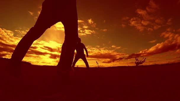 dva muži fotbalista hrát s míčem venku během západu slunce silueta zpomalené video. muži hraje Evropský fotbal na přírodě západ slunce silueta životní styl