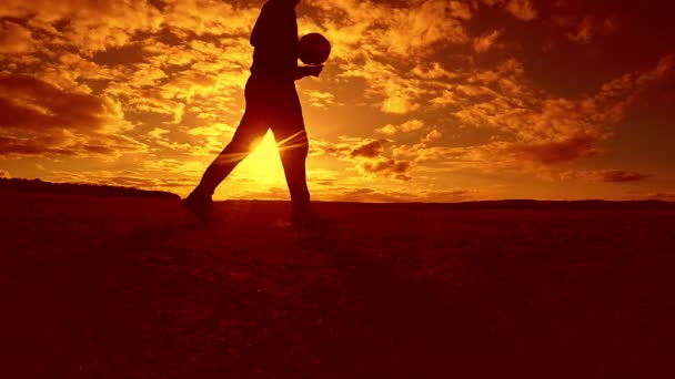 soccer player stuffing ball silhouette man kicks ball in the air with lifestyle sunset background. man playing soccer at sunset nature sunlight silhouette outdoors slow motion video