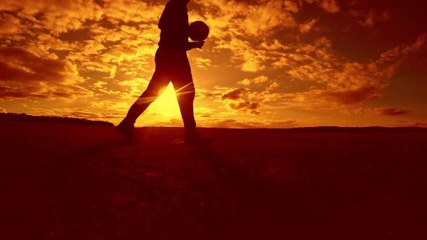 fotbalista nádivka míč siluetu člověka kopne míč ve vzduchu s slunce pozadí životního stylu. člověk hrát fotbal na západu slunce přírodní sluneční světlo silueta venku zpomalené video