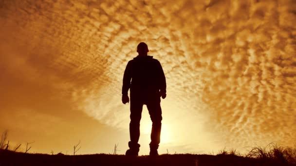Sagoma di un uomo con le mani sollevate nel tramonto concetto di religione, di culto, di preghiera e di lode. sagoma di un uomo alla natura di tramonto di una mano nel partito del sole. concetto di libertà e di vittoria