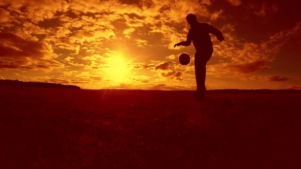 soccer player stuffing ball silhouette man kicks ball in lifestyle the air with sunset background. man playing soccer at sunset nature sunlight silhouette outdoors slow motion video