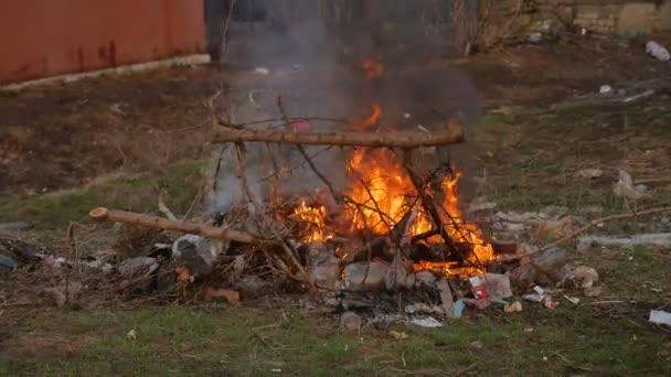 Fuoco della fiamma morbida e smog è bruciare immondizia o rifiuti su sfondo scuro. Incenerimento dei rifiuti provoca linquinamento dellaria e il riscaldamento globale. Le fiamme sono arancio rossastro, a seconda del tipo di carburante