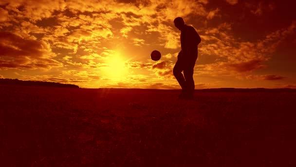 Fußballer stopft Ball Silhouette Mann tritt Ball Lifestyle in der Luft mit Sonnenuntergang Hintergrund. Mann spielt Fußball bei Sonnenuntergang Natur Sonnenlicht Silhouette im Freien Zeitlupe Video