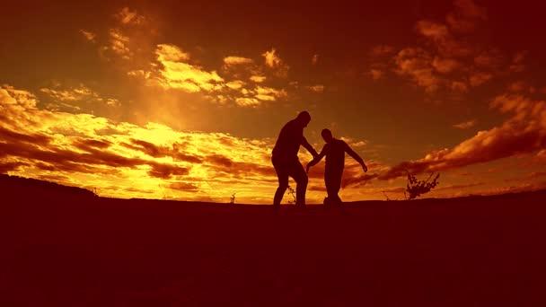 dva muži fotbalista hrát s míčem venku během západu slunce silueta zpomalené video. muži hraje Evropský fotbal na sluneční světlo slunce životní styl přírodní siluetu
