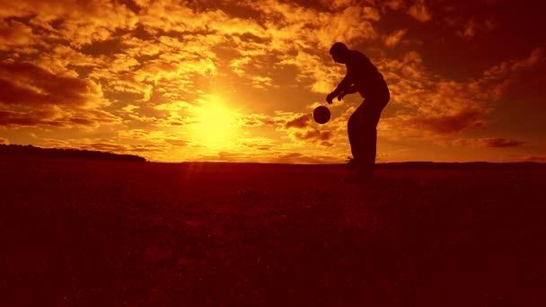 fotbalista nádivka míč siluetu člověka kopne míč ve vzduchu s slunce životní styl pozadí. člověk hrát fotbal na západu slunce přírodní sluneční světlo silueta venku zpomalené video