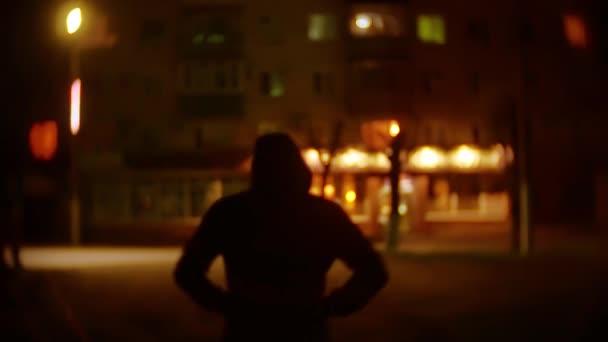 silueta lupič muž v kapuci je noční světlo lucerny zloděj pachatele. Neznámý lupič rozmazané pozadí goes venku bandita v kapuci lupič
