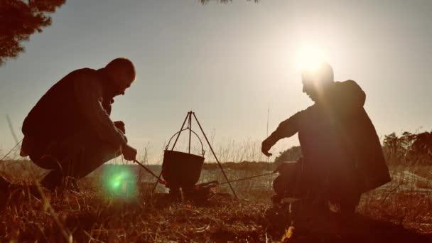 Dva turisté životní styl piva sedí oheň pěší strana v přírodě kemp silueta slunce západ slunce. dva muži silueta zastavení na slunci dovolenou kotel světla ohně kapoty párky